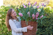 Young lady carrying basket with spring flowers