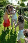 Children and parents playing with water in the garden