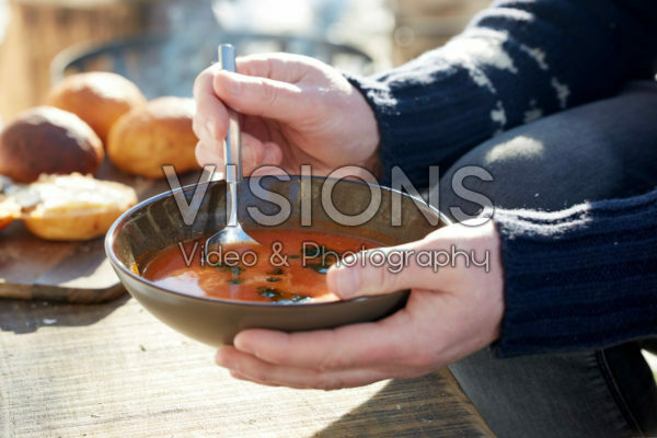 Holding bowl of tomato soup