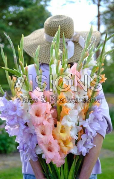 Lady holding bunch of gladioli