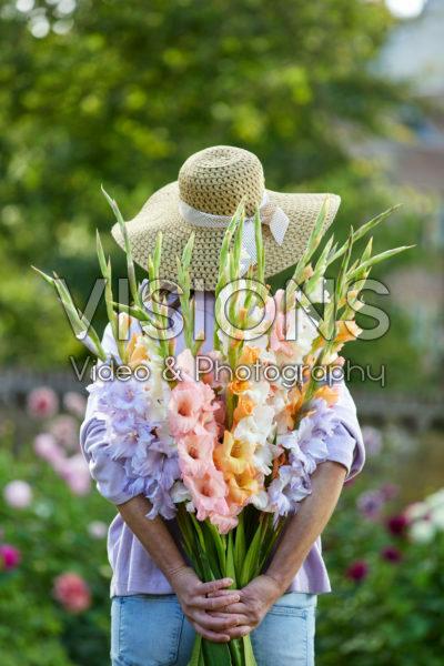 Dame met bos gladiolen